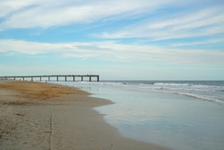 People walking along St Augustine Beach with pier in the background.