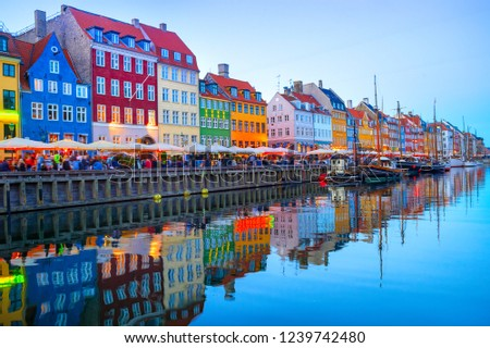People walking and sitting in restaurants at illuminated Nyhavn embankment by canal with moored boats in evening dusk, Copenhavn, Denmark Foto stock ©