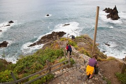 people walking and watching the view on access trail to the below beach with sharp lava rock peaks in the surf, high waves and steep coastal scrub landscape