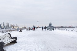 People walking down the pier with landed warcrafts and a lighthouse in Kronshtadt, Saint Petersburg, Russia.