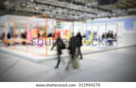 People walking during an event, intentionally blurred post production background.