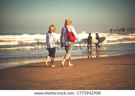 People walking on a beach. Adult people walking, on a sunny day, at the beach.