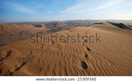 people walking on a sand dune - stock photo