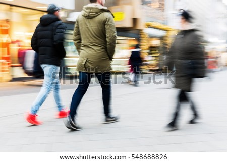 people walking on a shopping street with camera made motion blur #548688826