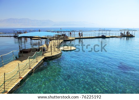 People walking on a wooden flooring at coast of the Red sea (Eilat. Israel)