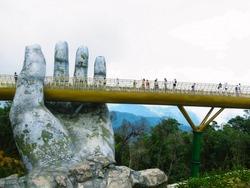 people walking on golden bridge in Ba Na Hills