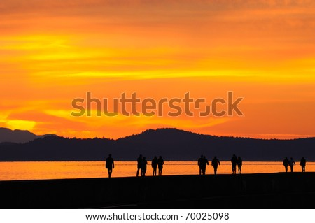 people walking on Ogden point breakwater in twilight, victoria, british columbia, canada