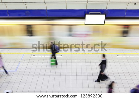 people walking on platform at a metro railway station with motion blur speed train and blank tv billboard, shot in Taipei, Taiwan, asia