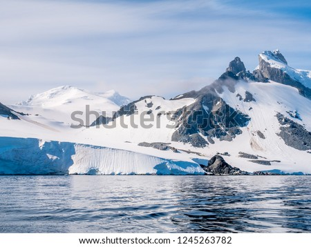 People walking on slope of Spigot Peak on Arctowski peninsula, Antarctic Peninsula, Antarctica #1245263782