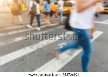 People Walking on Zebra Crossing. Blurred Background.