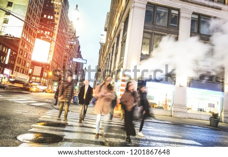 People walking on zebra crossing on West 31th st in Manhattan - Crowded streets of New York City during rush hour in urban business area - Warm desaurated filter with blurred motion on pedestrians stock photo