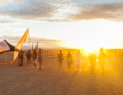 People walking towards sunset at a festival in the desert