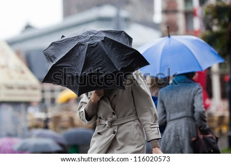 people walking with umbrellas in the rainy city