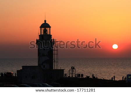 people watching the sunset near an ancient lighthouse during the sunset