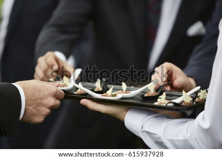 People wearing formal clothes eating appetizers. Waiter serving food. Close up picture. Unrecognizable men.  #615937928