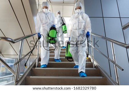 People wearing protective suits disinfecting stairs with spray chemicals to prevent the spreading of the coronavirus