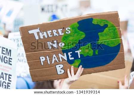 People with banners protest as part of a climate change march #1341939314