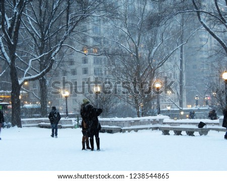 People with covered up in winter gear faces are taking pictures in front of Central Park in a heavy snow fall. Manhattan, New York City, USA.