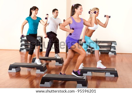 people with dumbbells on step boards in gym