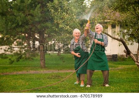 People with hose having fun. Cheerful senior couple in garden. Make it rain.