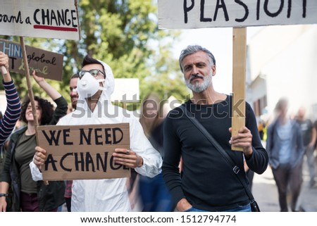 People with placards and protective suit on global strike for climate change.