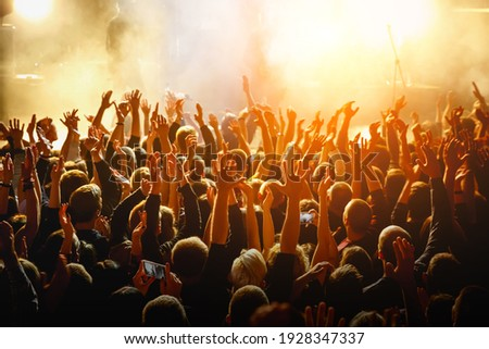 People with raised hands at a public event. Gathering in concert hall