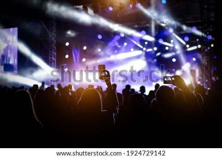 People with raised hands, silhouettes of concert crowd in front of bright stage lights Stockfoto ©