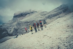 people with technical mountain clothing while observing a mountain in front of them