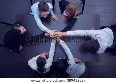 Shutterstock People with their hands together. Business team work concept