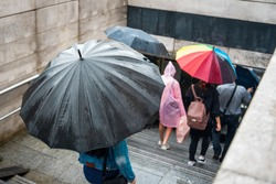 People with umbrellas descend into the underpass. Cityscape on a rainy day. Umbrella with raindrops. Bad weather. City scenes in the rain.
