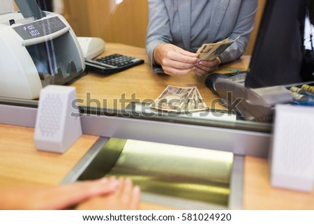 people, withdrawal, saving and finance concept - clerk counting cash money for customer at bank office or currency exchanger #581024920