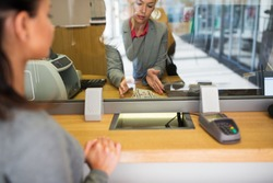 people, withdrawal, saving and finance concept - clerk with cash money and customer at bank office or currency exchanger