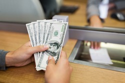 people, withdrawal, saving and finance concept - customer hands with cash money at bank office or currency exchanger