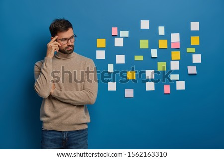 People, work, thoughts concept. Contemplative bearded guy keeps finger on temple, looks pensively aside, puts colorful sticky notes on wall, thinks on ideas to write, develops marketing plan alone