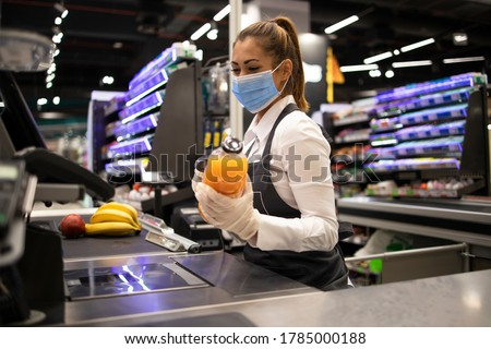 People working during global virus pandemic. Cashier at supermarket wearing mask and gloves fully protected against corona virus. Foto d'archivio ©