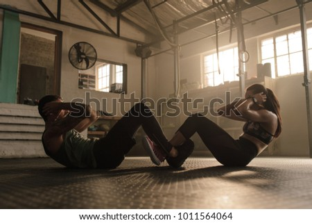 People working out in gym. Fit man and woman doing sit ups together.