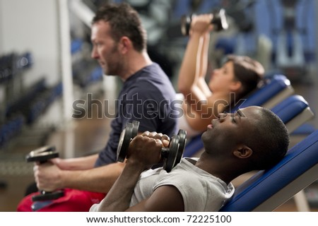 People working out with weights at health club stock photo