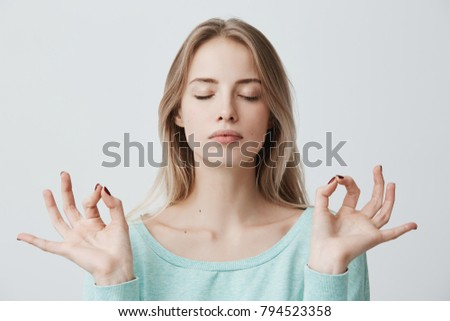 People, yoga and healthy lifestyle. Gorgeous young blonde woman dressed in light blue sweater keeping eyes closed while meditating indoors, practicing peace of mind, keeping fingers in mudra gesture #794523358