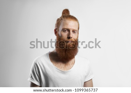 People, youth, style and fashion concept. Picture of handsome positive trendy looking young redhaired hipster guy with fuzzy beard and hair knot posing in studio, dressed in casual white t-shirt