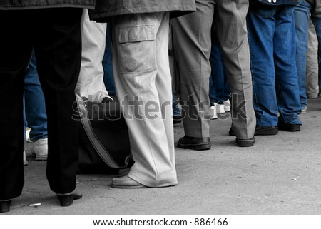 Peoples legs, wearing trousers and jeans. Desaturated with only the jeans saturated. - stock photo