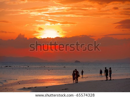 peoples on beach look to sunset