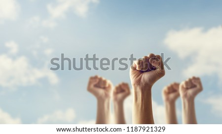 Photo of  Peoples raised fist air fighting and sunlight effect, Competition, teamwork concept, background space for text.