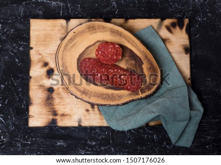 Peperoni on wooden board ready to season a pizza. The main ingredients of pepperoni are pieces of beef and pork, which are mixed and seasoned (mostly peppers of various types.