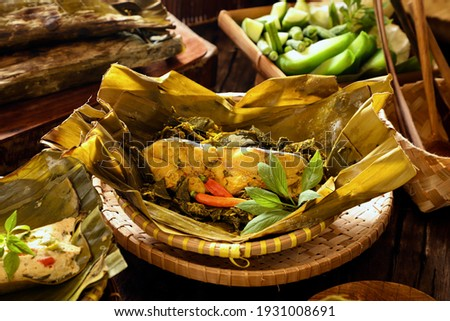 Pepes Ikan Tenggiri. Steamed Spanish mackerel with spices and cassava leaves in banana leaf parcel. Foto d'archivio ©