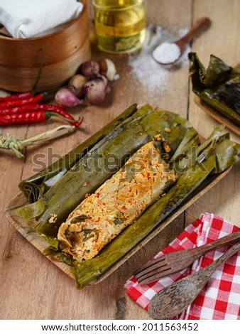 Pepes Tahu Jamur, seasoned tofu and mushroom, wrapped in banana leaves then steamed and then grill a while.  Serving on wooden table.  Foto d'archivio ©