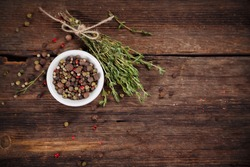 Pepper and thyme on wooden board