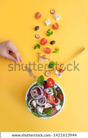 Pepper being sprinkled into a summer salad with feta cheese, kalamata olives and tomatoes