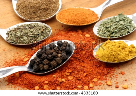 pepper in a spoon with six other spices - stock photo