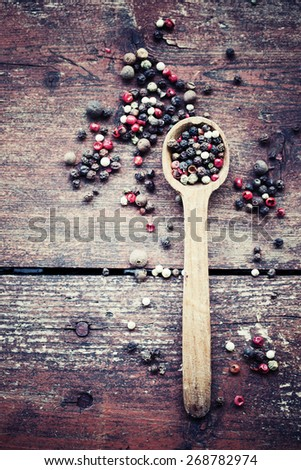 pepper in wooden spoon/ mixture of peppers hot pepper, red pepper, black pepper, white pepper, green pepper, background