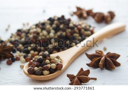 pepper in wooden spoon/ mixture of red pepper, black pepper, white pepper, green pepper